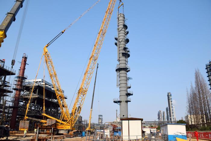 图为27日下午,施工人员正在吊装分馏塔