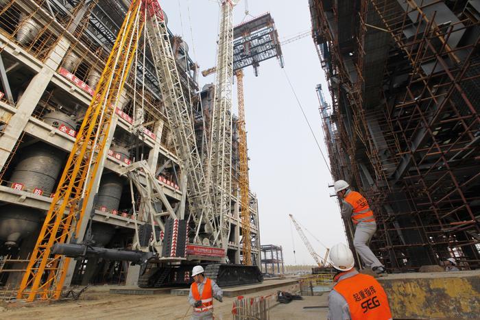 中国石化新闻网讯(赵天奇) 12月5日,中安联合煤气化装置气化框架钢结构模块首件吊装一次成功。 本次吊装的钢结构模块,是经过地面组对后的大型钢结构框架,三轴两跨六根立柱,模块总长22米,宽11米,共计两层平台,钢结构总重186.9吨,加上平台钢格栅、劳动保护、防腐、防火层、照明灯等附属设备,总重量达200余吨。   为保证200余吨的大家伙能安全地被吊起并成功安装到66米高的平台上,中安联合项目管理部与工程建设单位在施工作业前进行了周密的策划,针对吊装对象体量巨大、作业环境狭小、交叉作业多等具体困难,